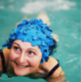 Elderly woman wearing a flower swim cap while swimming.