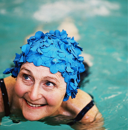 Elderly woman wearing a flower swim cap while swimming.