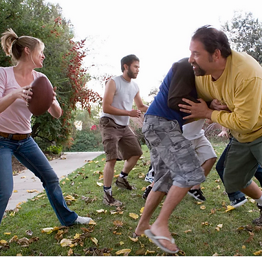50 year old parents play football with their 3 adult sons in thier back yard.