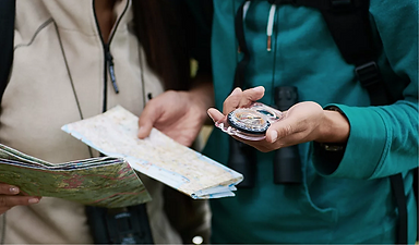 Two people traveling with a compass and a map