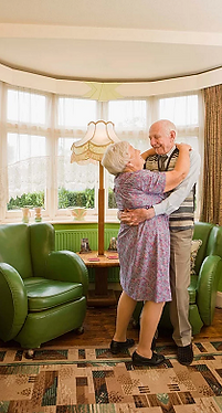 Elderly couple embrace eachother while dancing in the living room.
