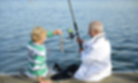 Grandpa teaching grandson to fish while sitting on a dock.