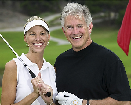 A 50 year old couple posing for a picture on a golf course.