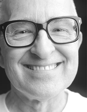 Elderly man smiling wearing big black glasses.
