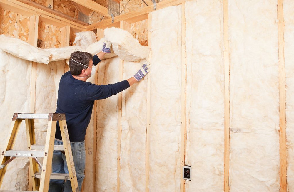 Insulating a stud wall.