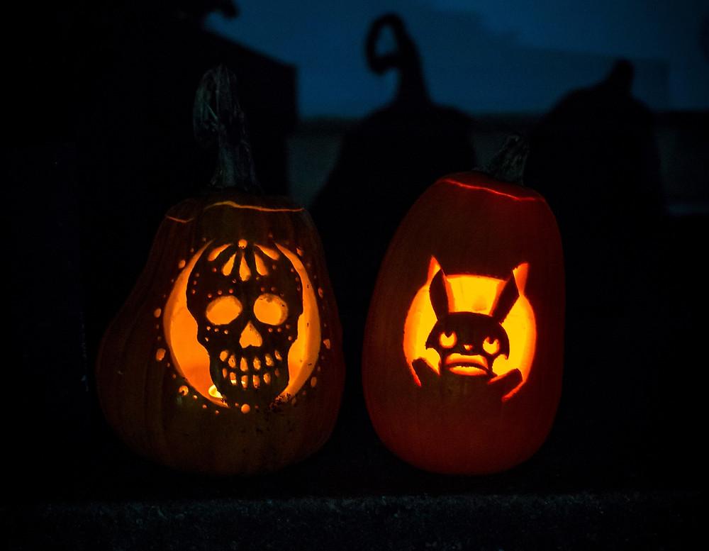 two pumpkin lanterns at night