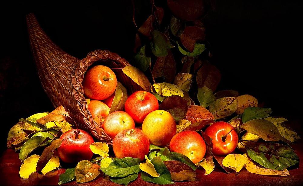 Cornucopia of apples and autumn leaves