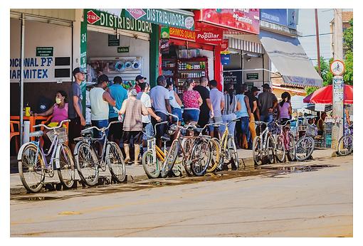 Uma fila de pessoas sai de um estabelecimento e avança ao longo da calçada. Encostadas na mesma calçada há várias bicicletas estacionadas em fila, gerando esta cena curiosa. Ao fundo, uma placa presa no poste tem o desenho de um ciclista, o que indica que ali tem uma ciclofaixa.