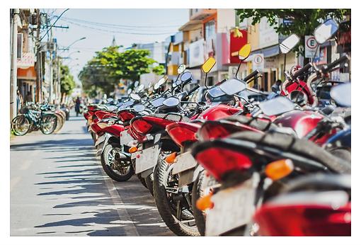 À esquerda está a ciclofaixa da Avenida do Comércio com algumas bicicletas estacionadas ao fundo. À direita há muitas motos estacionadas. O alinhamento da imagem está no nível das lanternas traseiras, dando destaque ao predomínio da cor vermelha na foto.
