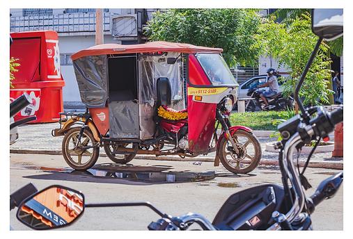 No primeiro plano aparece o guidão e os retrovisores de uma moto que emolduram o tuk-tuk vermelho parado na praça. A frente da moto tem um pára-brisa que também serve de apoio para o teto do tuk-tuk. O banco do motorista tem encosto e o acento, uma capa colorida.