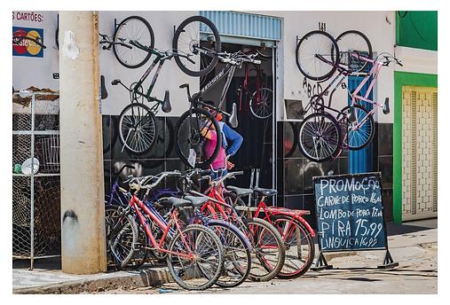 Uma loja tem quatro bicicletas expostas na calçada e outras quatro penduradas na parede da fachada. Bem na frente da loja há uma placa preta escrita em branco com os preços da promoção... do açougue! A promoção é para a carne de porco, lombo de porco, pira e linguiça.