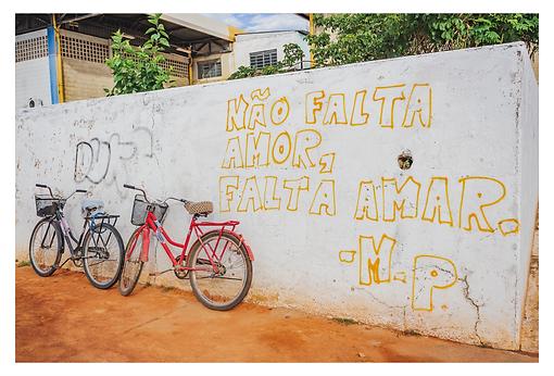 """Em um grande muro branco há duas bicicletas com cestinhos encostadas no muro e à esquerda da imagem: uma é preta e a outra vermelha. O destaque é a frase pintada em amarelo ocupando o espaço da altura do muro: """"Não falta Amor, falta Amar."""" Assinado por M.P."""
