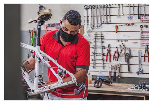 Um mecânico faz a manutenção da bicicleta. Ele é moreno, veste uma calça branca, blusa vermelha com detalhes em preto e, em tempo de pandemia, uma máscara de proteção na cor preta.