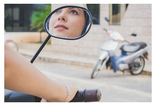 Uma motociclista vista de trás, onde se vê uma parte do braço, a mão segurando a manopla da moto e no retrovisor, o reflexo do seu belo rosto que olha para a frente. O que ela vê é outra moto azul e prateada estacionada perpendicularmente à calçada da frente, à esquerda.
