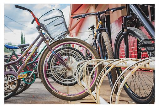 Em um ângulo visto mais de baixo avista-se à direita uma estrutura metálica em semi-arcos para o estacionamento de bicicletas. Na frente, a roda da primeira bicicleta emoldura as outras rodas das bicicletas mostrando vários círculos e aros alinhados.