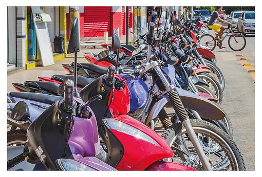 Várias motos estão estacionadas na mesma posição. Há diversos modelos, cores e elas estão tão limpas e brilhantes que parecem que estão expostas para a venda. Ao fundo à direita há carros aguardando a sua vez de seguir em frente, enquanto um ciclista atravessa a rua.
