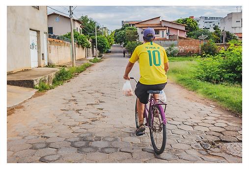 """A imagem é de um homem em uma bicicleta passando por uma rua de paralelepípedos, vestindo a camisa amarela nº 10 da seleção brasileira com o nome do """"Neymar Jr"""" estampada nas costas. Ele transporta sacolas no guidão da bicicleta, onde é possível ver que em uma delas está cheia de pequi dentro."""