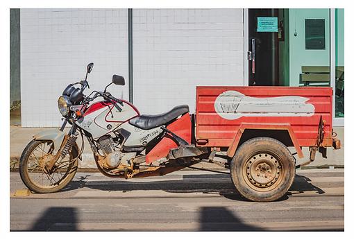 Parada na rua há uma moto que foi modificada para ter uma carreta permanente. A moto não tem a roda traseira e a carreta está fixada a ela em sua extensão. A moto é branca com detalhes em vermelho e a carreta é vermelha com detalhes em branco.