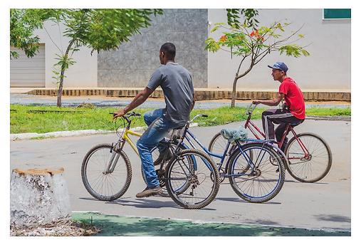 Pela avenida passam dois rapazes e três bicicletas. Um dos rapazes conduz uma outra bicicleta além da sua. O banco da bicicleta que está sendo levada está envolvida em um saco plástico, o que pode indicar que eles a estejam levando para o conserto.