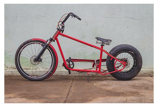 Encostada em uma parede verde bem clara está uma bicicleta vermelha personalizada. Por ser mais rebaixada, com o guidão inclinado e os pedais mais à frente, a posição de quem a pedala é diferente das demais. O pneu traseiro é bem estiloso e mais largo que o da frente.