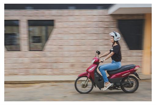 Uma moto pilotada por uma moça aparece com efeito de movimento, com o fundo mais borrado. Em uma moto vermelha à direita da imagem, uma moça com longos cabelos castanhos-escuro, veste sapatilha rosa claro, calça jeans, blusa preta e um capacete branco.
