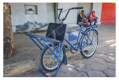 Uma bicicleta cargueira azul está estacionada ao lado da calçada. O dono bate um papo tranquilo com o amigo mais ao fundo à direita. Eles estão sentados no degrau de uma porta metálica fechada. À esquerda, o tronco de uma árvore e ao fundo as paredes são cinza e vermelha.