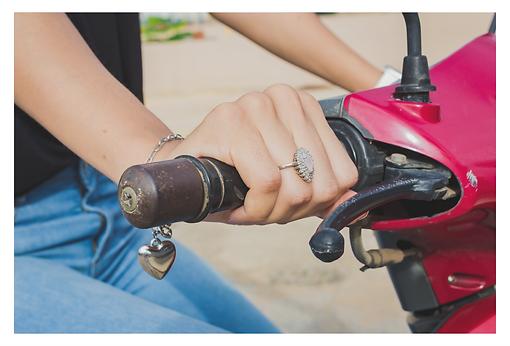 A imagem detalha a mão direita feminina segurando a manopla da moto. No dedo anelar há um anel prateado com pequenas pedrinhas brancas que juntas tem o formato de uma gota e no centro, uma pedra um pouco maior rosada. No pulso, uma corrente com um pingente em forma de coração prateado.