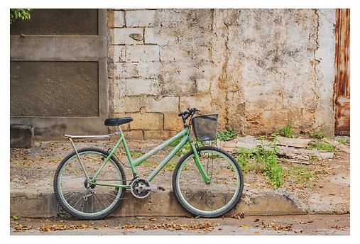 Há uma bicicleta verde claro com um cesto na frente estacionada ao lado do meio fio da calçada. Ao fundo, dois  muros mostram texturas rústicas: um é chapiscado com molduras lisas e o outro tem blocos aparentes e um reboco não finalizado . À direita aparece um pedaço do portão enferrujado