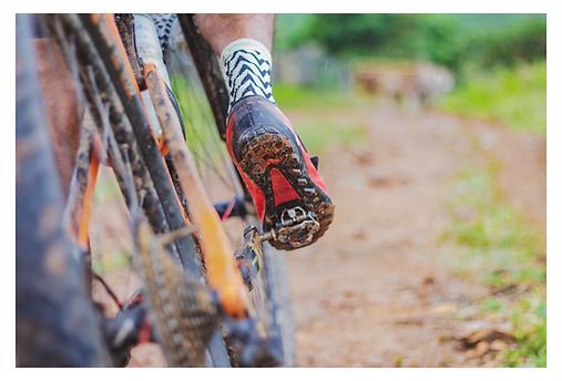 O ciclista está em uma trilha. Da esquerda até o meio da foto avista-se em um plano mais baixo, os pneus da bicicleta, a perna, o pé apoiado no pedal e um pouco de barro na bicicleta e na sola do sapato. O foco está no pé e no pedal. O restante aparece um pouco desfocado.