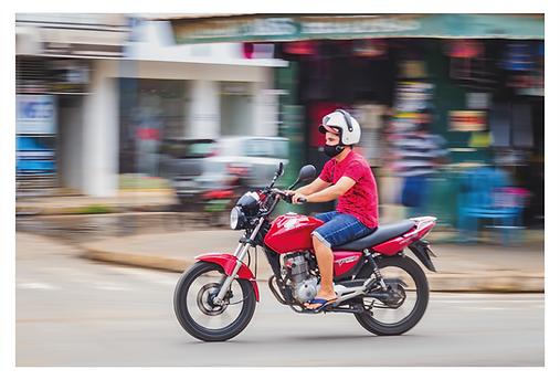 Um motociclista passando pela rua está focado na imagem. O fundo desfocado e borrado dá a sensação de foto em movimento. A moto e a camiseta do rapaz são vermelhas. Ele veste uma bermuda jeans, um boné marrom e um capacete branco por cima do boné