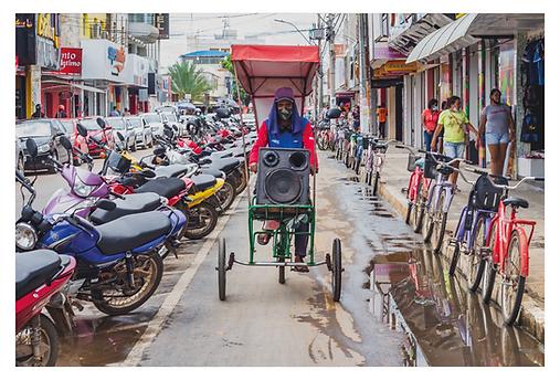 Uma bicicleta passa pela ciclofaixa da Av. do Comércio carregando uma caixa de som. A bicicleta tem um pequeno toldo para proteger o condutor do sol. Do lado direito há bicicletas estacionadas e do lado esquerdo, motos e carros estacionados cada qual no seu espaço.