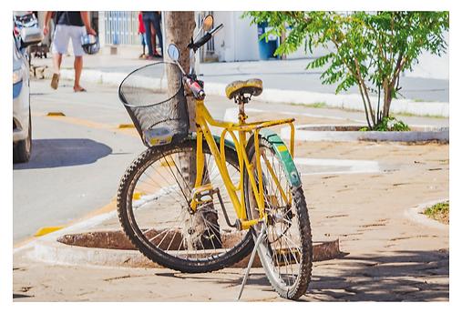 Debaixo da sombra de uma árvore no centro da cidade, há uma bela bicicleta estacionada, cuja pintura é em verde e amarelo. A bicicleta também tem um cesto e retrovisores. Percebe-se a passagem de um carro no canto da foto e das pernas de algumas pessoas passando ao fundo.