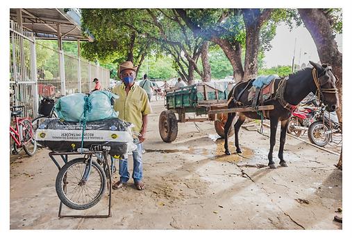 Do lado de fora do Mercado Municipal, um senhor está em pé ao lado da sua bicicleta com dois grandes volumes no suporte da frente. Ele usa um chapéu de couro e máscara de proteção. No lado esquerdo há uma charrete puxada por um cavalo na calçada e algumas motos estacionadas na rua.