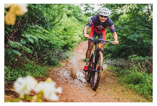 Descendo por uma trilha em curva leve e com muito verde em volta, o ciclista passa por uma poça d'água em velocidade, espirrando lama para os lados. A inclinação da foto acompanha a curva da trilha. No pneu da frente há lama e no rosto do ciclista um sorriso.