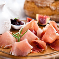 Dry cured ham with olives and fig on cho