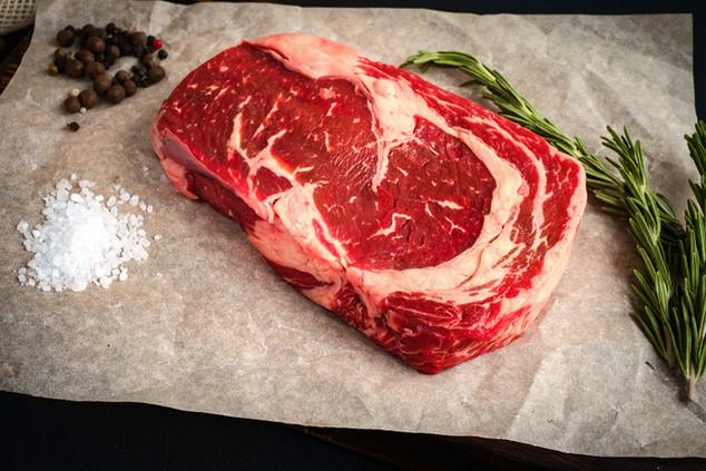 raw ribeye steak lying on Kraft paper ar