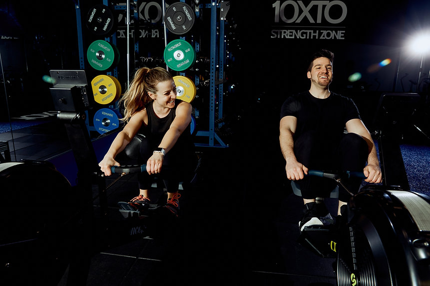 Man and woman on rowing machines laughing
