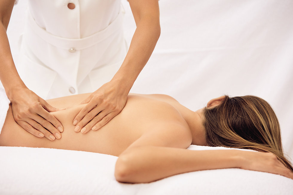 Woman in treatment room receiving a back massage from therapist.