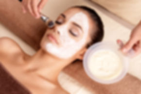 Relaxed woman getting a facial while an esthetician applies a mask on her face