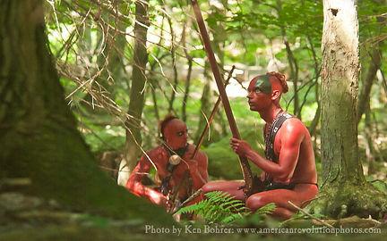 Native American reenactors in war paint during an ambush of American troops in New York