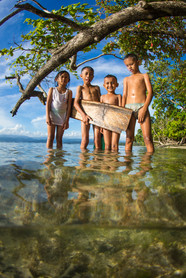 Local kids with wooden surfboard