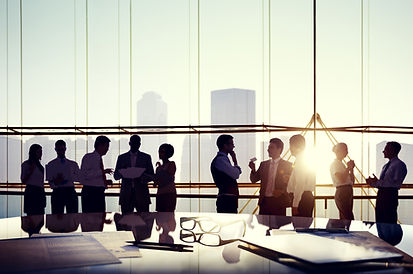 Business people at a conference table overlooking a city