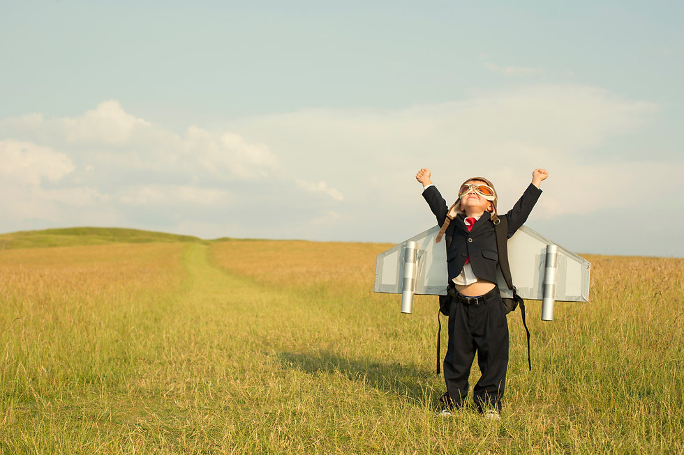 Child looking triumphant reaching up to the sky wearing wings