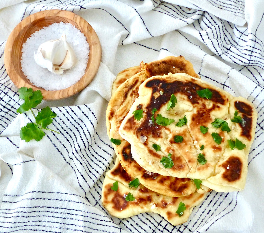 Naan bread garnished with garlic butter.