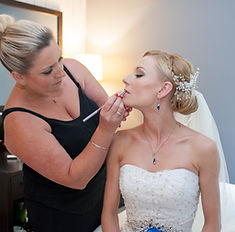 Lizzy Westney applying makeup to a bride