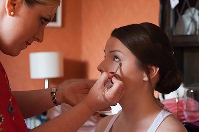 Lizzy applying bridal makeup