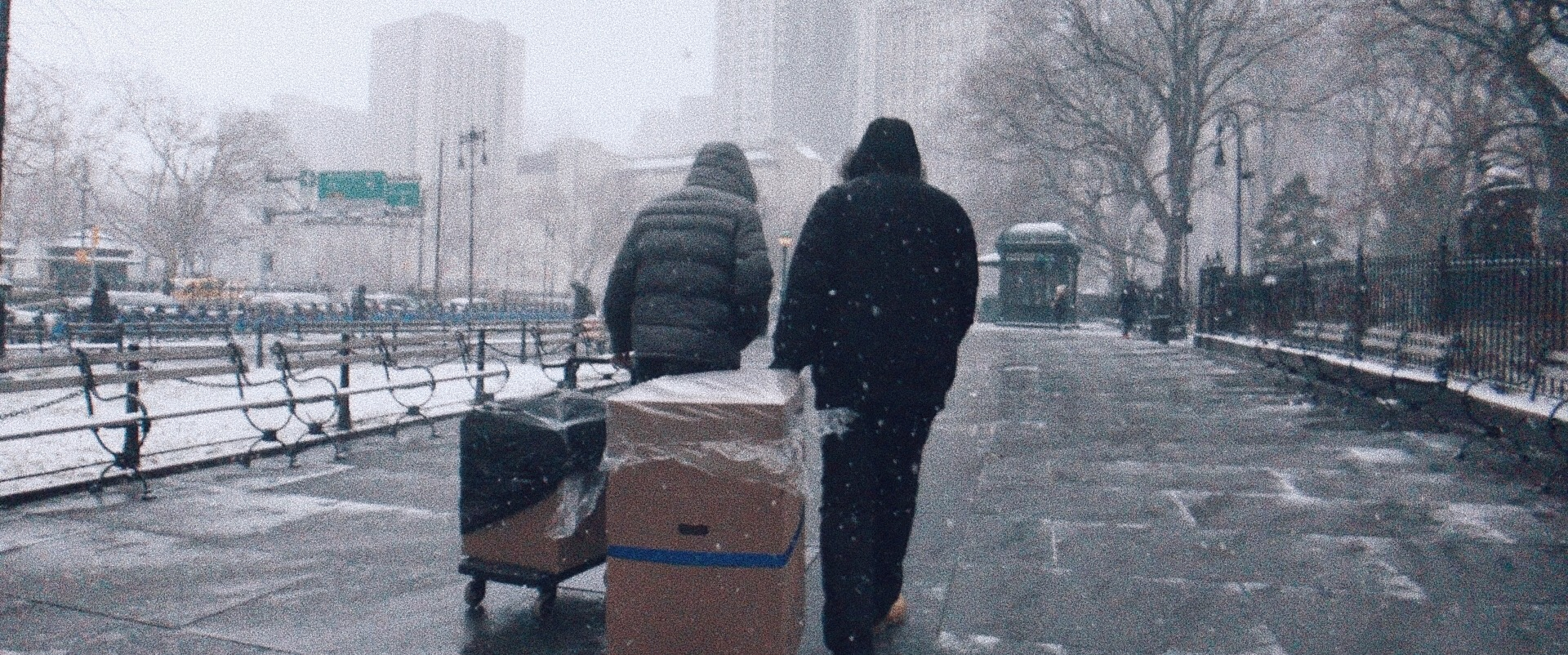 Two people pulling package carts in snowy Manhattan.