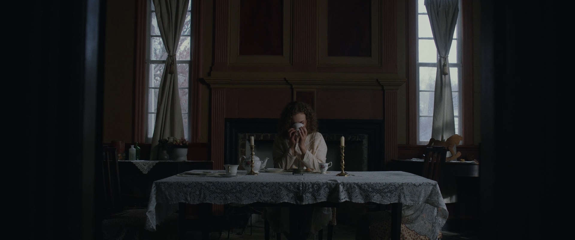 A girl sips tea at her dining table.