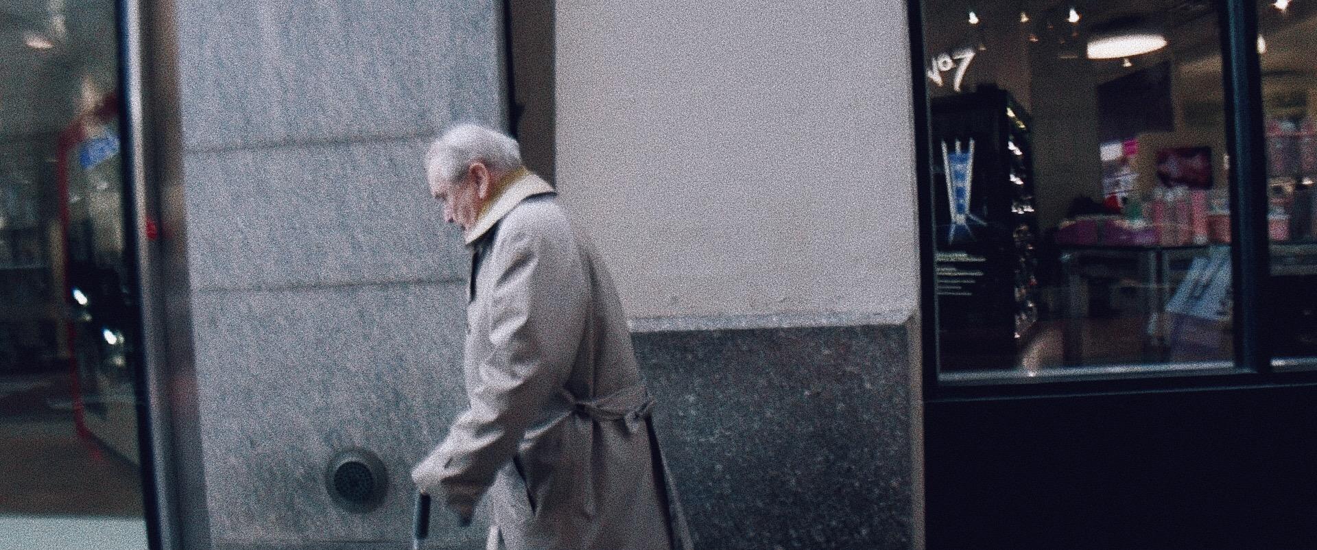 An elderly man walking in front of a concrete wall.