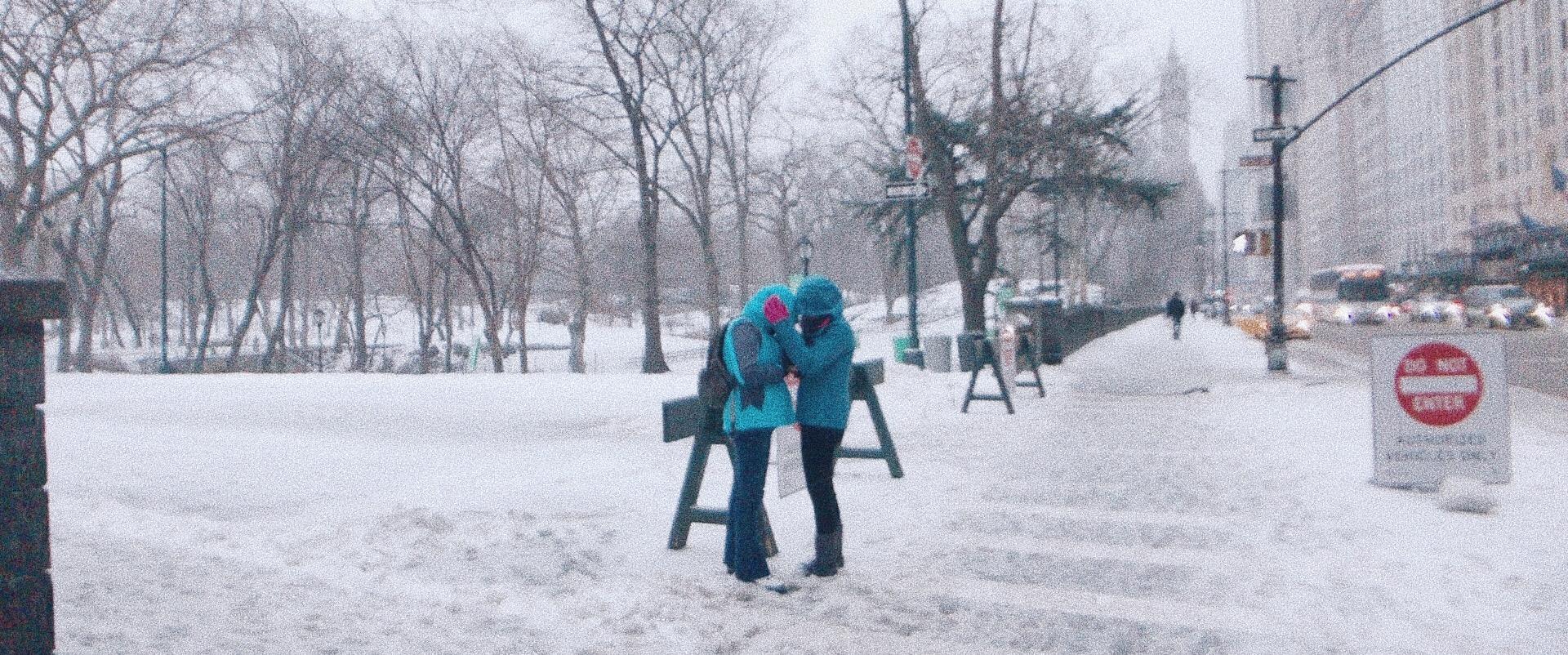 Two people embrace on a crosswalk in snowy Manhattan.